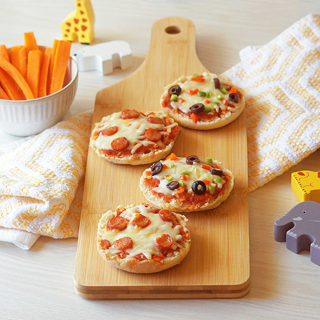 Mini pizzas topped with peperoni, cheese and olives served with cut up carrots