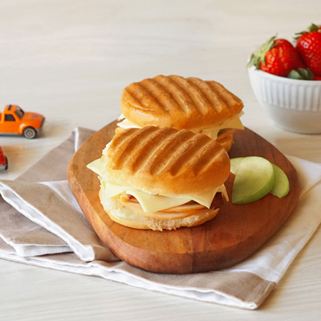 : Grilled turkey and cheese Panini sandwiches, served with sliced apples