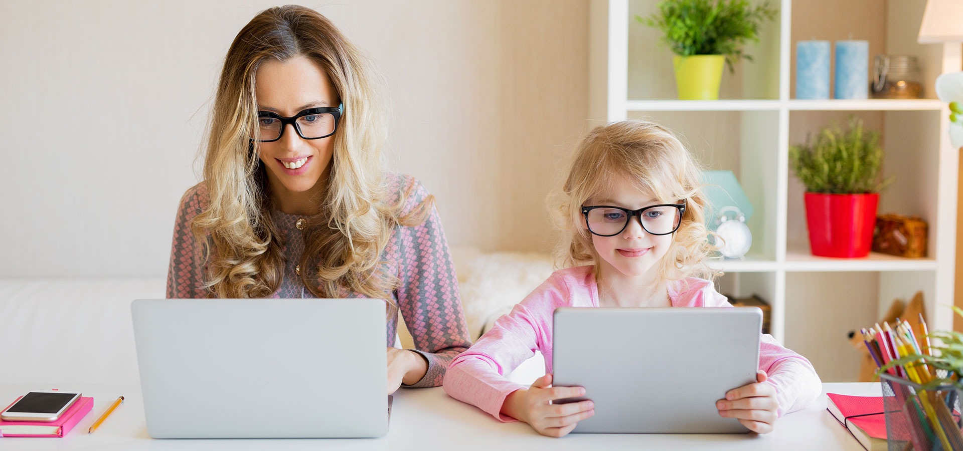 Mother and daughter sitting at table, both on laptops working