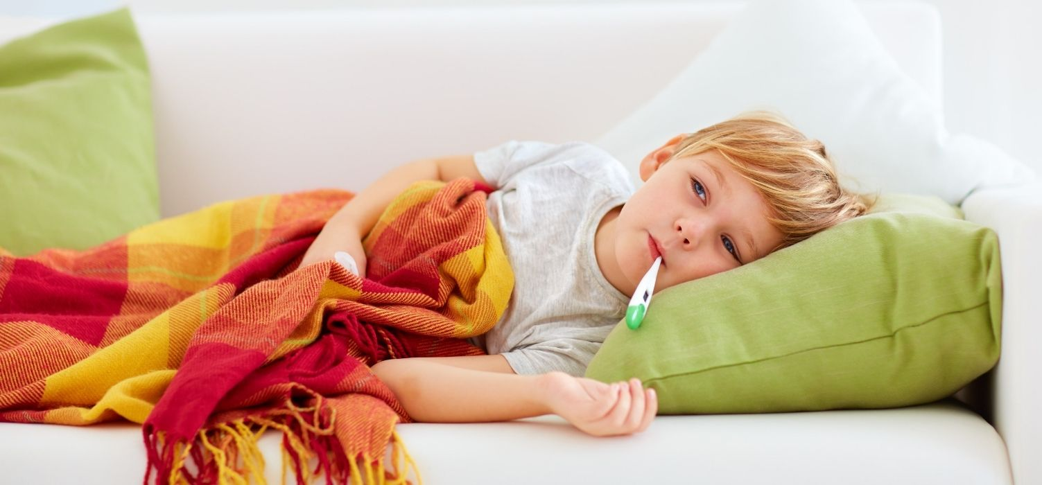 Wonder Bread Sick Day Tips- Young sick boy laying on couch with thermometer in mouth
