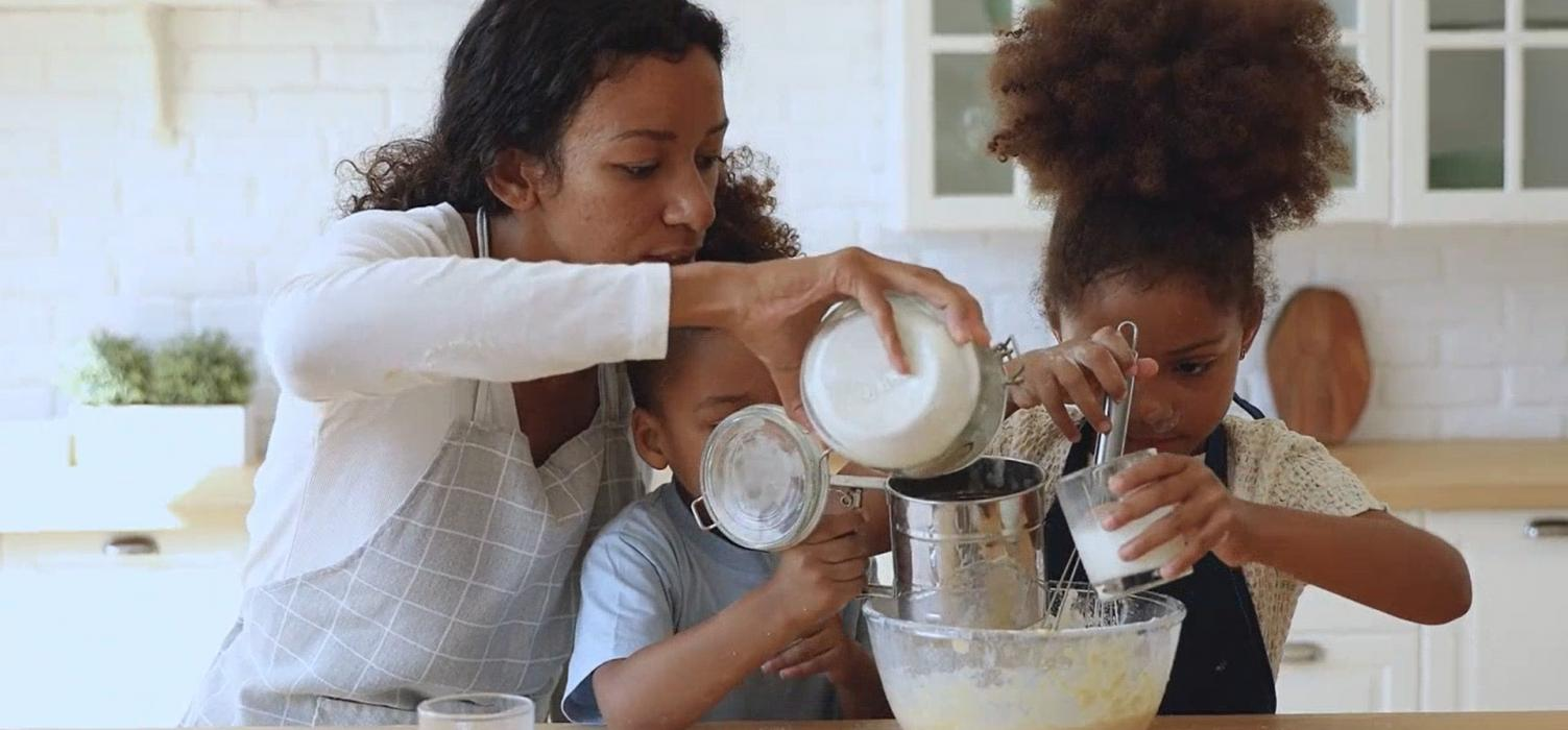 Mother with two daughters in kitchen, measuring flour
