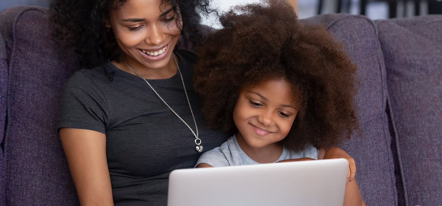 Mother and daughter, smiling while on laptop