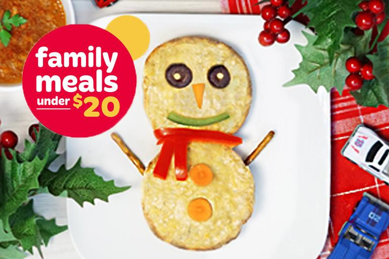 Two English muffins topped with tuna salad, cheese, black olives, carrot, green pepper slice, two pretzel sticks and 2 slices of baby carrots to create a snowman